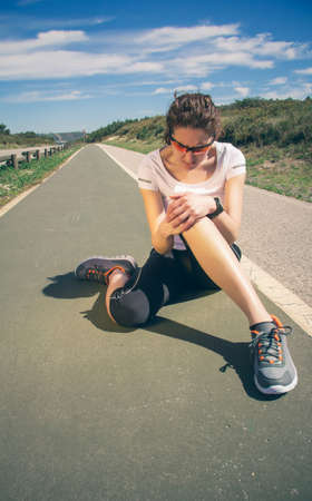 Athletic young woman in sportswear touching her knee by painful injury during a training outdoors. Sport injuries concept.