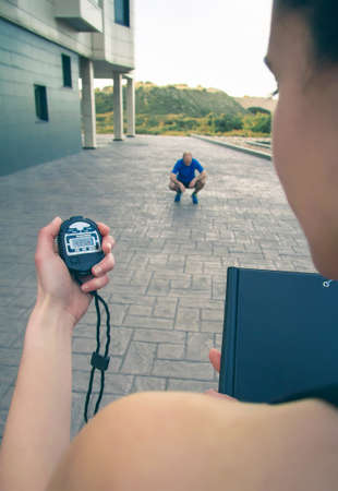 Closeup of woman trainer hand using a chronometer to timing at tired athletic man in a hard training outdoors photo