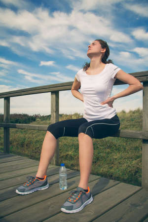 cramp: Athletic young woman in sportswear sitting touching her lower back muscles by painful injury, over a nature background. Sport injuries concept. Stock Photo