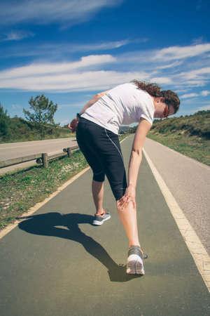 운동에 젊은 여자 운동복 고통을 고통에 그녀의 다리 종아리 근육 경련 훈련에 의해 고통을 다시보기. 스포츠 부상 개념입니다. 스톡 콘텐츠