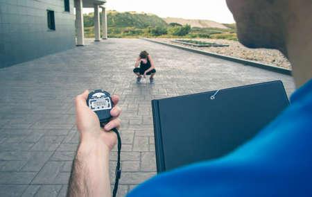 タイミングにクロノメーターを使用して屋外でハード トレーニングで疲れて運動若い女性で男トレーナーの手のクローズ アップ