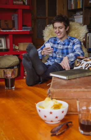 men socks: Young man laughing and looking smartphone sitting on a chair at home. Teenager leisure time concept.