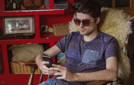 Young man relaxing and looking smartphone sitting on a chair at home. Teenager leisure time concept. photo