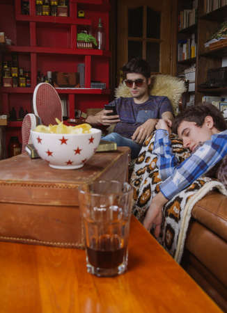 drinking problem: Young man sleeping on a sofa and friend looking his smartphone in a bored day at home. Teenager leisure time concept.
