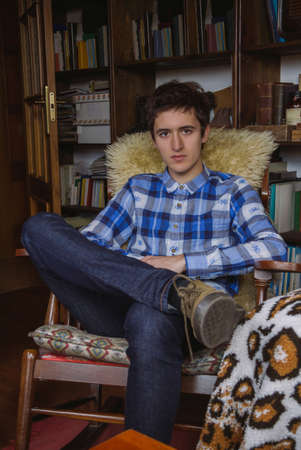 young man jeans: Portrait of serious young man with blue plaid shirt and jeans sitting on a rocking chair at home