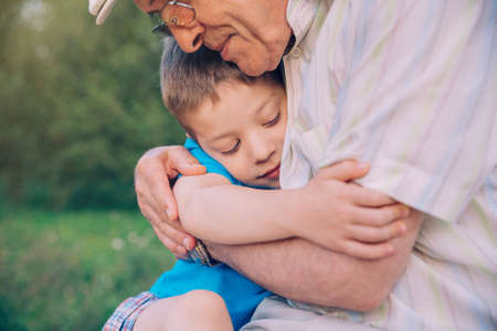 grandparent: Portrait of happy grandson hugging grandfather over a nature outdoor background. Two different generations concept. Stock Photo