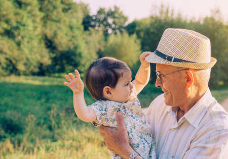 Adorable baby girl playing with the hat of senior man over a nature background. Two different generations concept. Archivio Fotografico