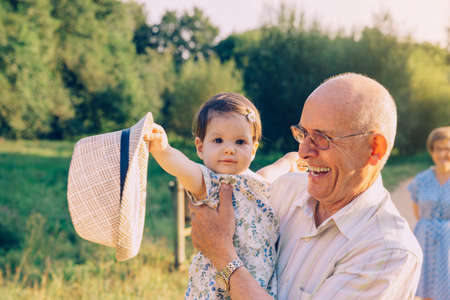 male senior adult: Adorable baby girl playing with the hat of senior man over a nature background. Two different generations concept. Stock Photo