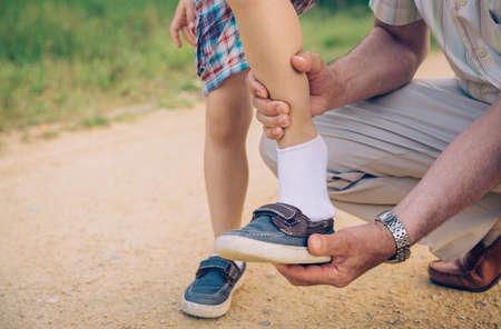 Closeup of grandfather putting shoe to his grandson over a nature pathway background Stockfoto
