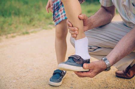 abuelo: Primer plano de abuelo poner el zapato a su nieto en un fondo vía naturaleza