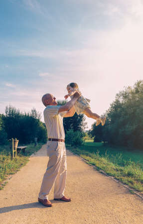 leisure time: Senior man playing with adorable baby girl over a nature background. Grandparents and grandchild leisure time concept. Stock Photo