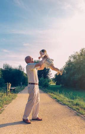 Senior Mann spielt mit adorable Baby Mädchen über einem Naturhintergrund. Großeltern und Enkelkind Freizeitkonzept.