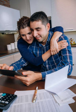 Cheerful young couple using digital tablet at kitchen home after the work. Family leisure home concept.