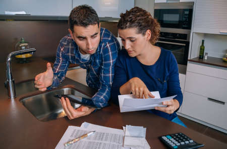 bank accounts: Serious young couple reviewing their bank accounts with a digital tablet and calculator at home. Financial family concept.