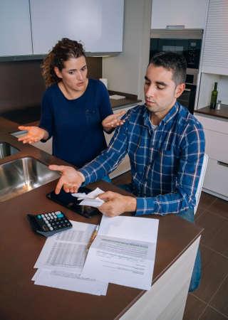 problemas familiares: Pareja de jóvenes desempleados con muchas deudas revisar sus cuentas. Concepto financiero de los problemas familiares. Foto de archivo