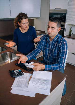 Unemployed young couple with many debts reviewing their bills. Financial family problems concept. photo