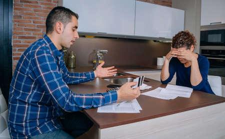 problemas familiares: Pareja joven desesperada y desempleados revisar sus deudas de tarjetas de crédito. Concepto financiero de los problemas familiares.