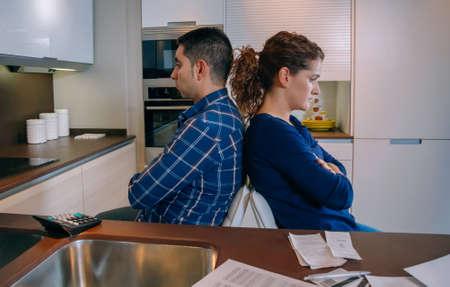 problemas familiares: Pareja joven enojado sentados espalda con espalda despu�s de una pelea dura por sus muchas deudas en casa. Concepto financiero de los problemas familiares.