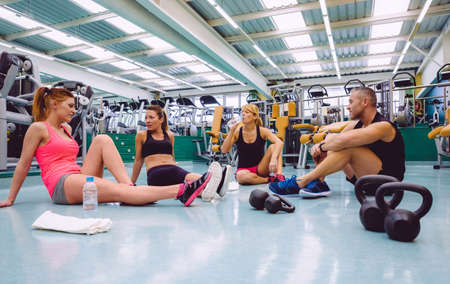 fitness center: Group of friends talking sitting on the floor of a fitness center after hard training day Stock Photo