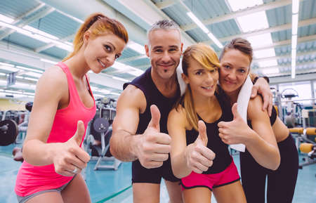 Group of friends with thumbs up smiling on a fitness center after hard training day. Selective focus on hands. Foto de archivo