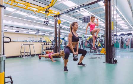 Grupo de mujeres hermosas entrenando duro en un circuito crossfit en el gimnasio Foto de archivo - 39560234