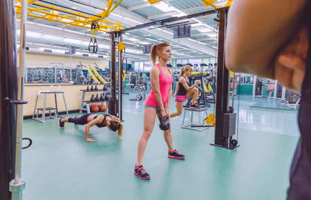 Back view of personal trainer looking at group of beautiful women training hard in a crossfit circuit on fitness center