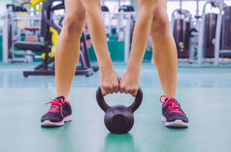 Closeup of beautiful woman ready to lift black iron kettlebell in a crossfit training on fitness center