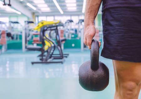 Primer plano de hombre atlético que sostiene kettlebell de hierro negro en un entrenamiento crossfit en el gimnasio