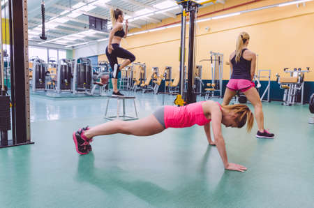 exercise equipment: Group of beautiful women training hard in a crossfit circuit on fitness center