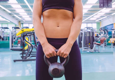 Closeup of beautiful woman with slim waist and black sportswear holding black iron kettlebell in a fitness center photo