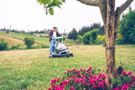 Portrait of senior man with cap mowing lawn with a lawnmower machine in a field