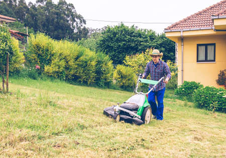 mowing grass: Portrait of young man with straw hat and plaid shirt mowing lawn with a lawnmower machine Stock Photo