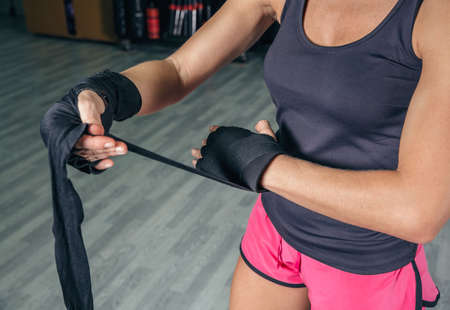 kickboxing: Closeup of beautiful woman wrapping his hands with protective bandages before boxing training in the gym