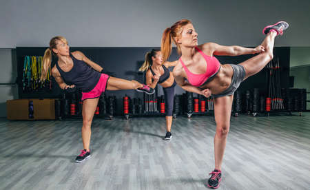 Group of beautiful women in a hard boxing class on gym training high kick