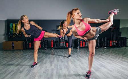 Gruppo di belle donne in una classe di pugilato duro allenamento in palestra alto calcio