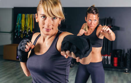Retrato de belas mulheres treinamento pesado de boxe no ginásio