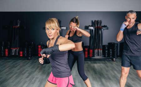 Grupo de pessoas em um treinamento de boxe duro no centro de fitness