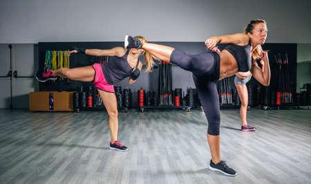 patada: Grupo de mujeres hermosas en una clase de boxeo duro en alta patada entrenamiento de la gimnasia