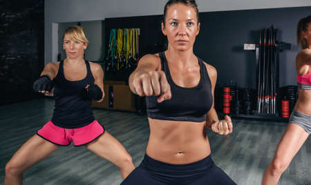 Group of beautiful women in a hard boxing class on gym training punch photo