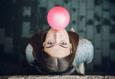 분홍색 풍선 껌을 불고 아름 다운 젊은 갈색 머리 십 대 소녀의 상위 뷰 스톡 콘텐츠