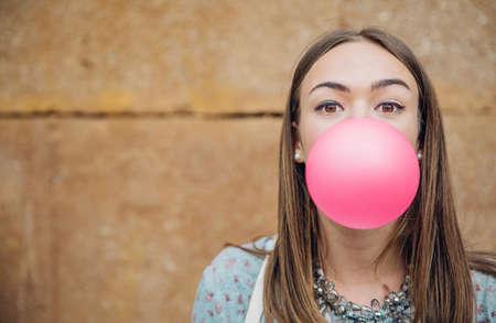 Gros plan de la belle jeune fille brune adolescente soufflant rose bubble gum sur un fond de mur de pierre