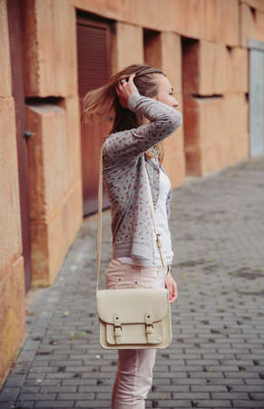 satchel: Fashion portrait of young trendy woman wearing gray jacket, pink jeans and white satchel bag over touching her hair outdoors Stock Photo