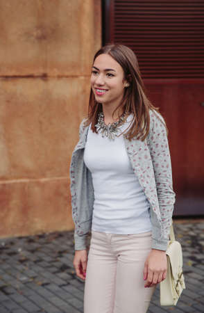 satchel: Closeup of young trendy woman wearing gray jacket, pink jeans and white satchel bag walking on the street