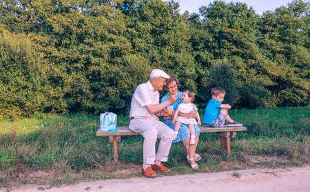 abuelos: Hombre mayor que la alimentación con puré de frutas para niña adorable mientras que un hermano celoso da la espalda sentado en un banco al aire libre. Abuelos y nietos relaciones concepto.