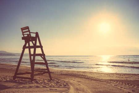 silla de madera: Silla de Baywatch en una hermosa playa vacía al atardecer de verano. Suave y tonos cálidos edición. Foto de archivo