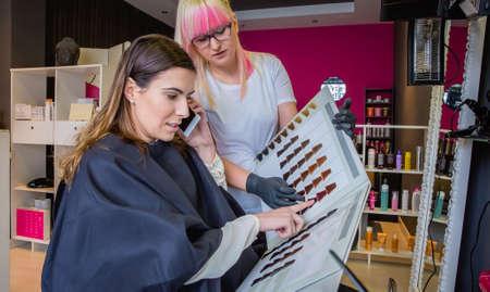 tinte de cabello: Joven y bella mujer mirando con peluquer�a una paleta tinte para el cabello, mientras que hablar por su tel�fono inteligente