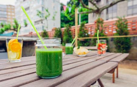 cocteles de frutas: batidos vegetales verdes y frutas infundidas cócteles de agua sobre una mesa de madera al aire libre. Concepto sano de las bebidas orgánicas verano. Foto de archivo