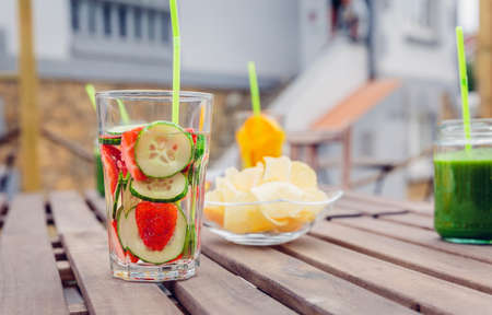 Infused fruit water cocktails and green vegetable smoothies over a wooden table outdoors. Healthy organic summer drinks concept.