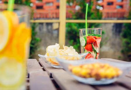 cocteles de frutas: Impregnado cócteles y aperitivos de agua de frutas tazones sobre una mesa de madera al aire libre. Concepto sano de bebidas de verano orgánicos.
