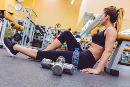 fitness center: Beautiful sporty woman resting sitting on the floor of fitness center and female friend doing exercises with dumbbells in the background. Selective focus on a dumbbles and bottle water.